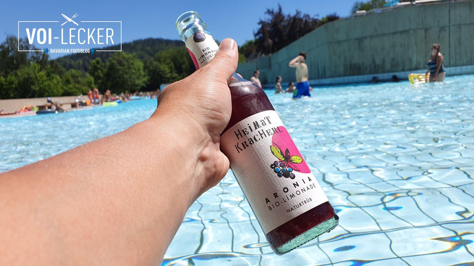 Eine Flasche Heimat Kracherl in der Hand vor einem Freibad